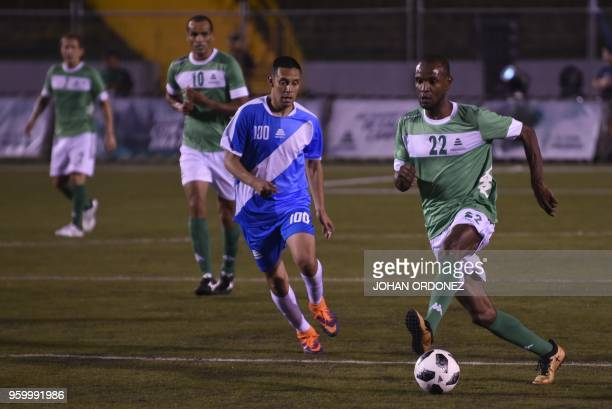 Former French footballer player Eric Abidal vies for the ball with fellow former footballer Guatemalan Claudio Albizuris during an exhibition match...