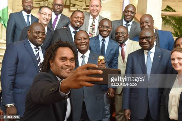 Former French international footballer Christian Karembeu takes a selfie with Ivory Coast's President Alassane Ouattara during the FIFA World Cup...