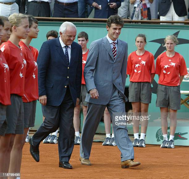 Former French Open Champion, Gustavo Kuerten of Brazil, enters court with Christian Bimes, President of the Federation Francaise de Tennis, to...