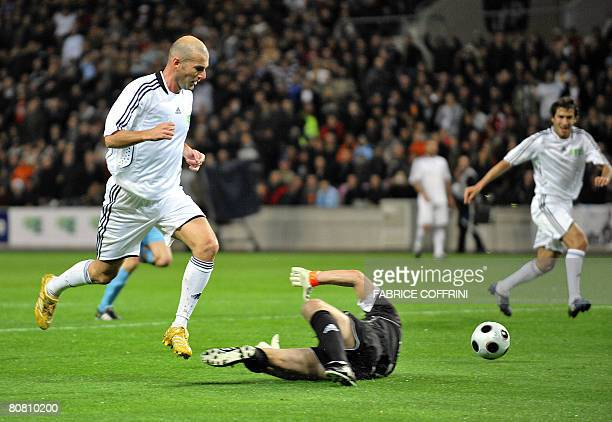 Former French player Zinedine Zidane passes a ball to former Uruguayan player Enzo Francescoli in front of former French goalkeeper Pascal Olmeta...