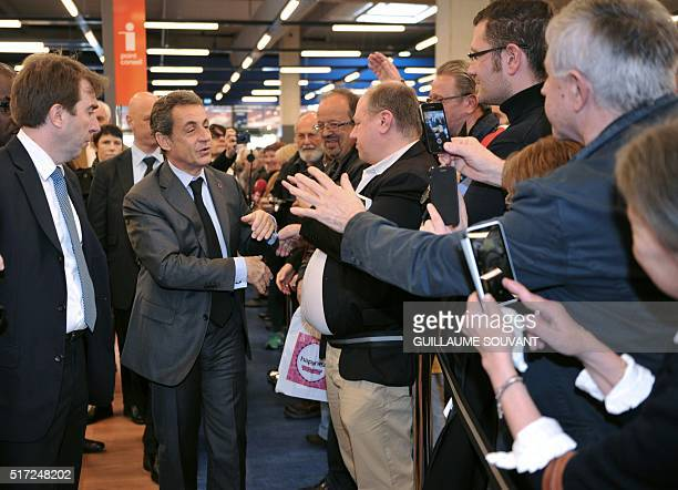 Former French President and leader of France's Les Republicains party Nicolas Sarkozy greets supporters at the Cultura shop on March 24, 2016 in...