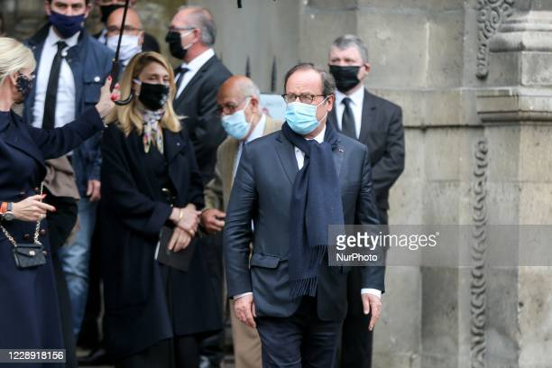 Former French President Francois Hollande and his partner French actress Julie Gayet leave after attending the funerals of French singer Juliette...