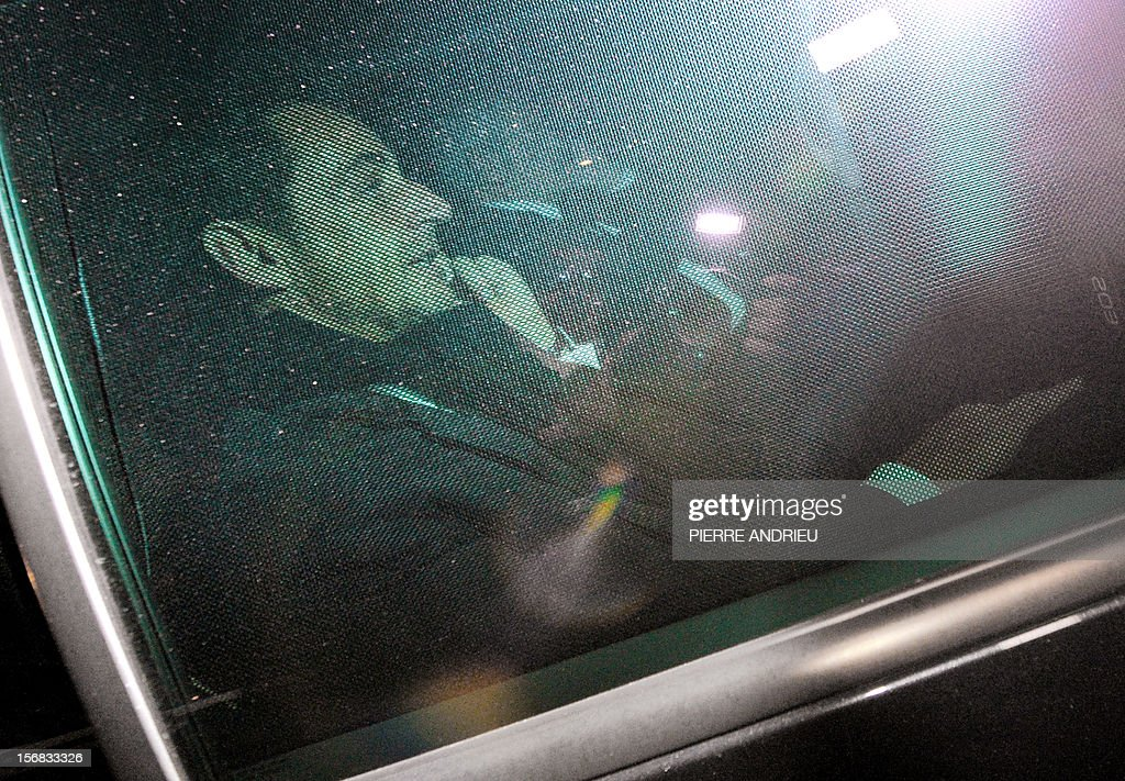 Former French president Nicolas Sarkozy (L) leaves the Bordeaux' courthouse in a car on November 22, 2012 at the end of a twelve-hour-long interrogation by the investigating judges, to respond to charges that his 2007 electoral campaign was financed with funds secured illegally from France's richest woman, Liliane Bettencourt. Sarkozy avoided indictment in illegal campaign financing case and prosecutors will continue to deal with him as a witness under caution, Sarkozy's lawyers said.