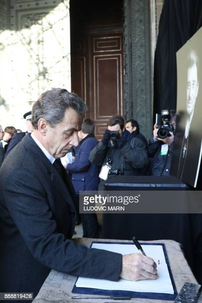 Former French President Nicolas Sarkozy signs the condolence book as he arrives at La Madeleine Church for the funeral ceremony in tribute to late...