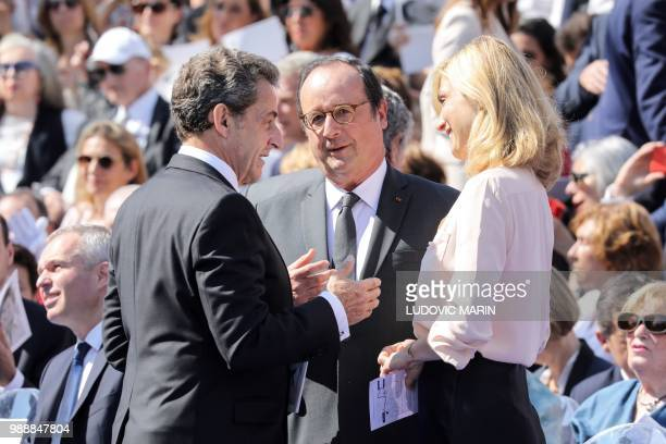 Former French President Nicolas Sarkozy talks with former French President Francois Hollande and his partner French actress Julie Gayet as they...