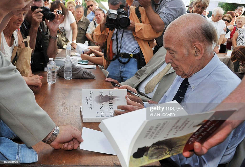 Former French President Valery Giscard d'Estaing (R) signs a copy of his book 'La princesse et le président' on August 26, 2012 in Chanceaux-pres-Loches, central France, as he participates in the 17th edition of 'La Foret des Livres' book fair.