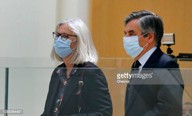 Former French prime minister Francois Fillon and his wife Penelope Fillon wearing protective face masks arrive for the verdict in their trial over a...