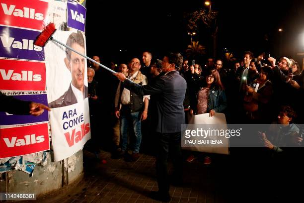 Former French prime minister Manuel Valls pastes a poster as he launches his electoral campaign to become Barcelona's next mayor in Barcelona on May...