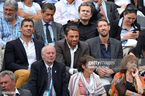 Former French Rugby players Jerome Thion Philippe Benetton and former French swimmer Alain Bernard attend the men's second round match between...
