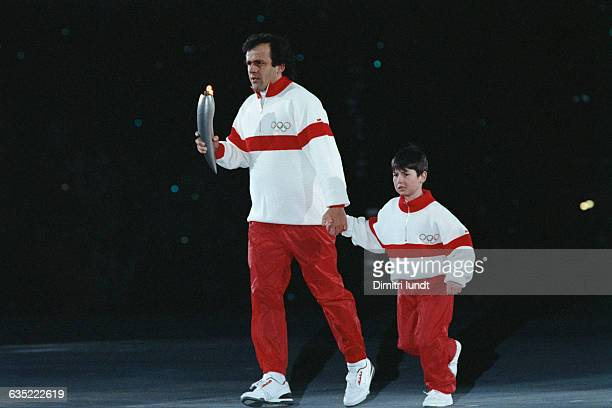 Former French soccer champion Michel Platini and Francois-Cyrille Grange walk with the Olympic torch during the 1992 Winter Olympic Games opening...