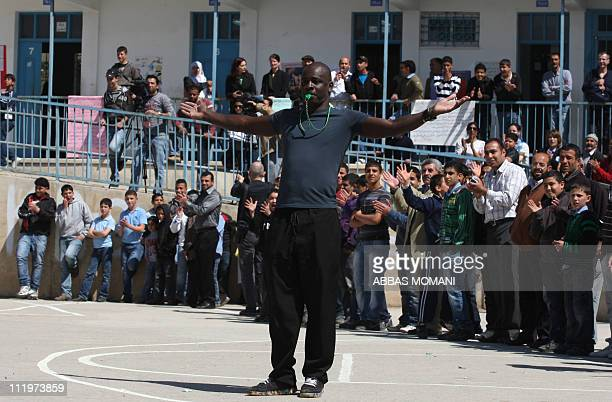 Former French soccer player Lilian Thuram whistles near Palestinian youngsters from the West bank refugee camp of Qalandia during a soccer friendly...