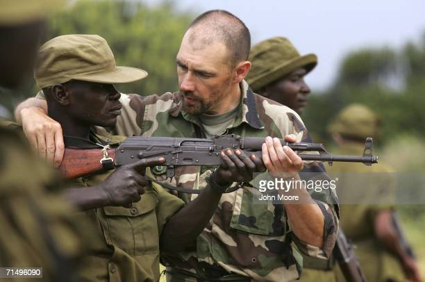 Former French special forces arms instructor Norbert Tible teaches a Congolese park ranger the use of an AK-47 assault rifle July 21, 2006 at Ishango...