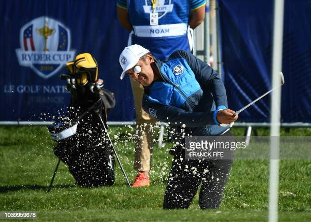 TOPSHOT Former French tennis player Yannick Noah plays a shot out of a bunker during a celebrity match ahead of the 42nd Ryder Cup at Le Golf...
