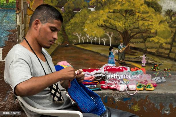 Former gang member crochets during a workshop at the prison of San Francisco Gotera, 161 km east of San Salvador on July 16, 2018. - Members of two...