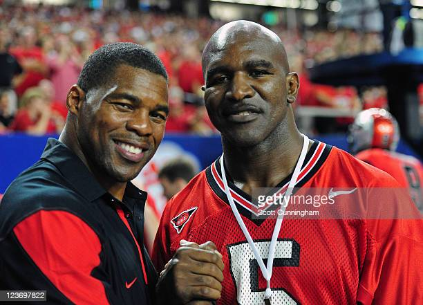 Former Georgia Bulldogs player Herschel Walker poses for a photo with boxer Evander Holyfield during the game against the Boise State Broncos during...