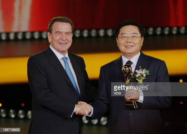 Former German Chancellor Gerhard Schroder poses with Xu Jianyi Chairman of China First Automobile Works Group Corporation during the 2011 CCTV China...