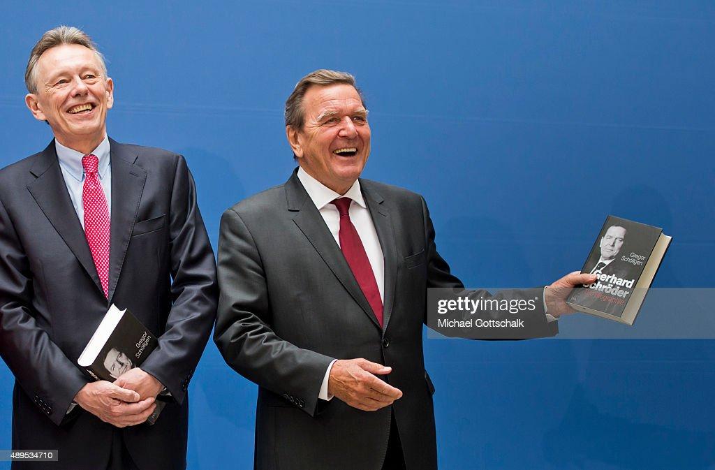 Former German Chancellor Gerhard Schroeder and German Chancellor Angela Merkel attends the presenation of 'Die Biographie' of 'The Biography' by biographer Gregor Schoellgen (L) on September 22, 2015in Berlin, Germany.