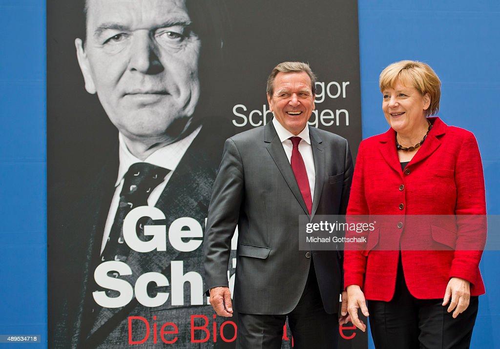 Former German Chancellor Gerhard Schroeder and German Chancellor Angela Merkel attends the presenation of 'Die Biographie' of 'The Biography' by biographer Gregor Schoellgen on September 22, 2015in Berlin, Germany.