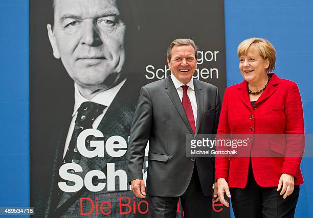 Former German Chancellor Gerhard Schroeder and German Chancellor Angela Merkel attends the presenation of 'Die Biographie' of 'The Biography' by...