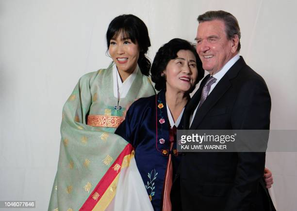 Former German chancellor Gerhard Schroeder his South Korean wife Kim Soyeon and her mother pose for a photo during their wedding party at the Adlon...