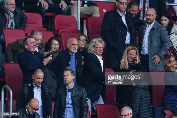 Former German chancellor Gerhard Schroeder sits happy in the stands next to Martin Kind chairman of Hannover during the Bundesliga match between FC...