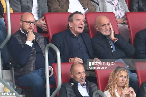 Former German chancellor Gerhard Schroeder sits in the stands next to Martin Kind chairman of Hannover during the Bundesliga match between FC...