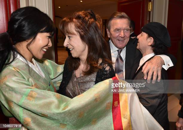 Former German chancellor Gerhard Schroeder speaks with Scorpions singer Klaus Meine while his wife Gabi speaks with Schroeder's South Korean wife Kim...