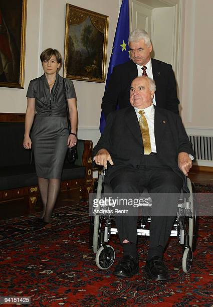 Former German Chancellor Helmut Kohl is pushed by an assistant and his wife Maike RichterKohl attend a private dinner at Bellevue Pallace on December...