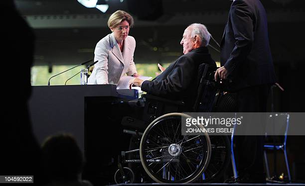 Former German Chancellor Helmut Kohl prepares to hold a speech while his wife Maike KohlRichter adjusts his documents during a celebration ceremony...