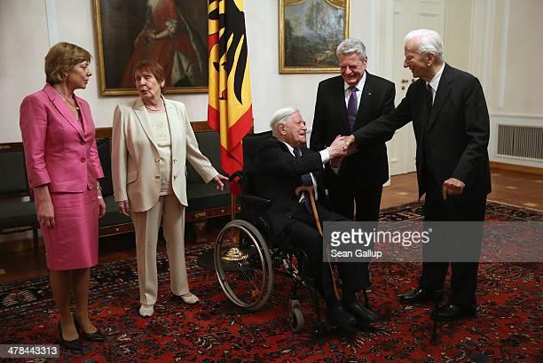 Former German Chancellor Helmut Schmidt greets former German President Richard von Weizsaecker as First Lady Daniela Schadt Ruth Loah and German...