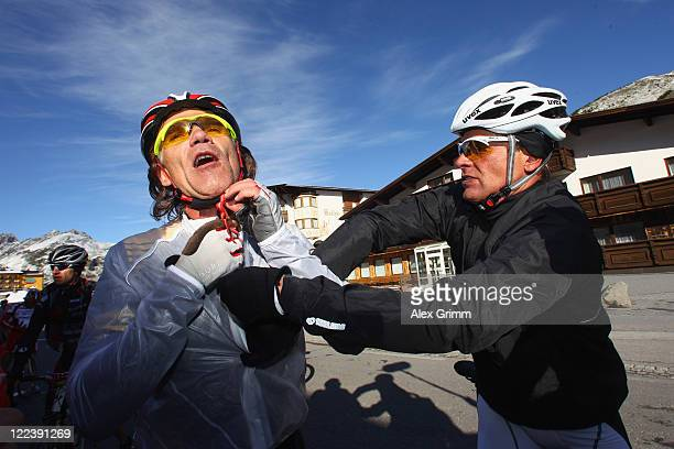 Former German cyclist Jan Ullrich helps his friend Frank Woerndl during a break at the Oetztaler Cycle marathon on August 28 2011 in Solden Austria