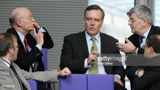 Former German Defense Minister Volker Ruehe speaks with current German Defense Minister Peter Struck and German Foreign Minister Joschka Fischer...