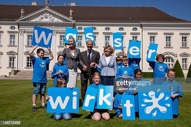 Former German First Lady Bettina Wulff Juergen Heraeus chairman of UNICEF Germany and current German First Lady Daniela Schadt pose surrounded by...