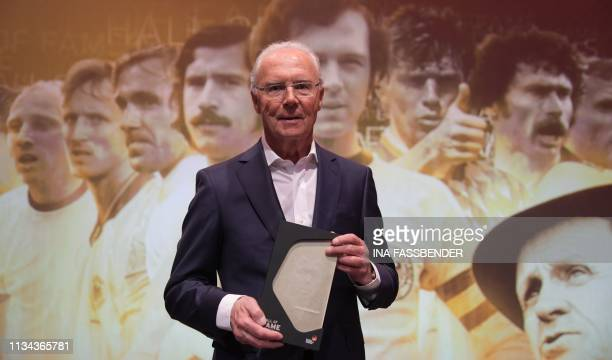 Former German football player Franz Beckenbauer holds his trophy as he attends the opening gala for the Hall of Fame of German Football at the German...