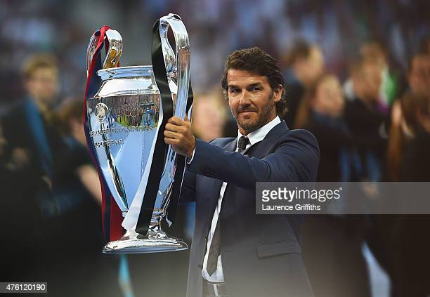 Former German footballer KarlHeinz Riedle holds the Champions League trophy during the UEFA Champions League Final between Juventus and FC Barcelona...