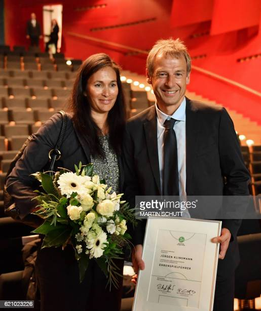 Former German national football team coach Juergen Klinsmann poses with his wife Debbie after he was named honorary captain of the German national...