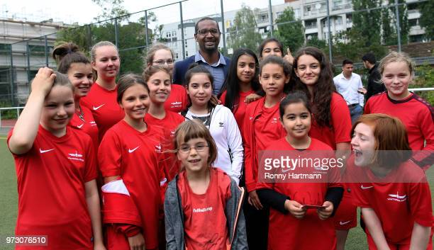 Former German National player Cacau poses with young girls during his visit of a program to encourage integration of children with foreign roots...