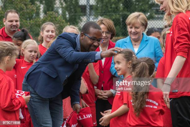 Former German National player Cacau receives a scarf from young girls during a visit of a program to encourage integration of children with foreign...