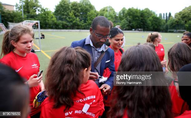 Former German National player Cacau signs autographs during his visit of a program to encourage integration of children with foreign roots through...