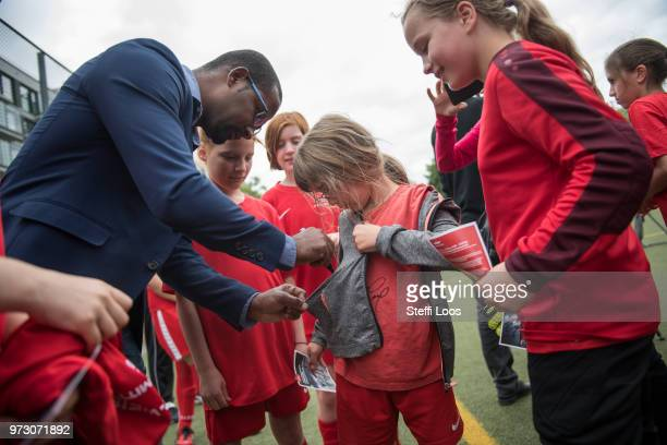Former German National player Cacau signs autographs for young girls during a visit of a program to encourage integration of children with foreign...
