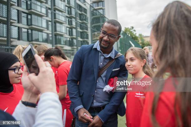 Former German National player Cacau takes a selfie with young girls during a visit of a program to encourage integration of children with foreign...