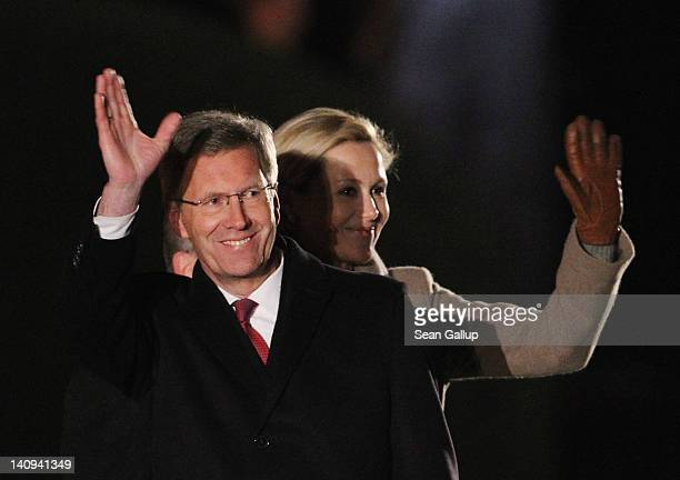 Former German President Christian Wulff and his wife Bettina wave goodbye at the conclusion of the Zapfenstreich or taps farewell ceremony for Wulff...