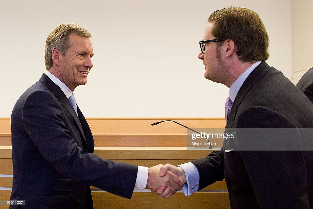 Former German President Christian Wulff greets defendant David Groenewold in the courtroom at the Landgericht Hannover courthouse for the second day of their trial on November 21, 2013 in Hanover, Germany. Wulff is accused of accepting favors while he was governor of Lower Saxony, a charge that prompted him to resign last year from his office as president. Wulff is the first post-World War II German president to face a court trial.