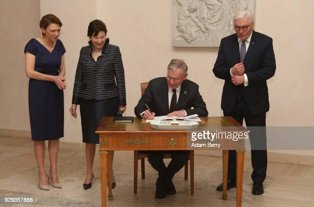 Former German President Horst Koehler signs a guest book as he attends a dinner in his honor during his 75th birthday next to Koehler's wife Eva...