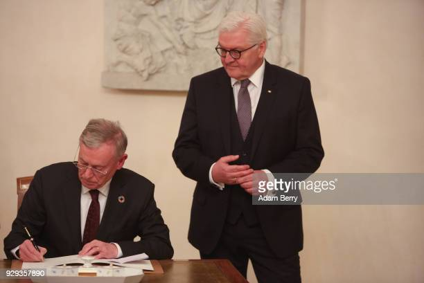 Former German President Horst Koehler signs a guest book as he attends a dinner in his honor during his 75th birthday next to German President...