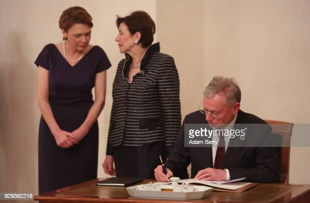 Former German President Horst Koehler signs a guest book as his wife Eva Luise Koehler and German President FrankWalter Steinmeier's wife Elke...