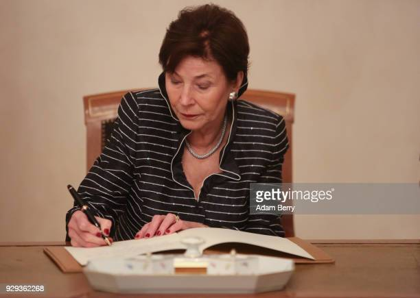Former German President Horst Koehler's wife Eva Luise Koehler signs a guest book at a dinner in her husband's honor during his 75th birthday at...
