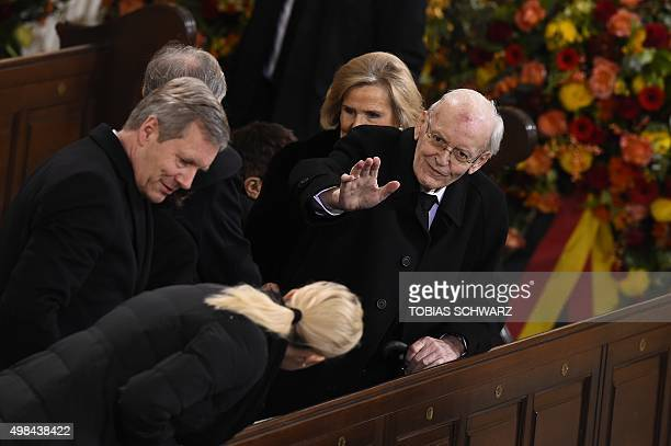 Former German President Roman Herzog waves as former German President Christian Wulff and his wife Bettina Wulff arrive for the state funeral for...
