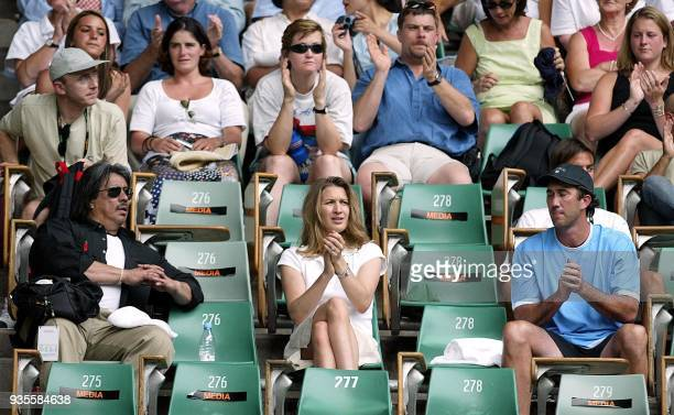 Former German women's tennis great Steffi Graf applauds as her husband Andre Agassi of the US wins a service game against Brian Vahaly of the US at...