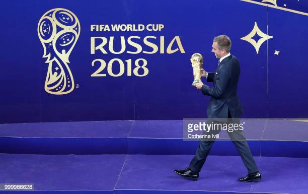 Former Germany football player Philipp Lahm takes the World Cup trophy to the stage after the 2018 FIFA World Cup Russia Final between France and...